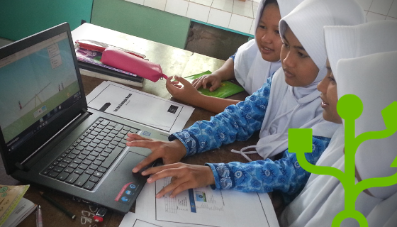 Four girls using one laptop. One of them is using the trackpad.